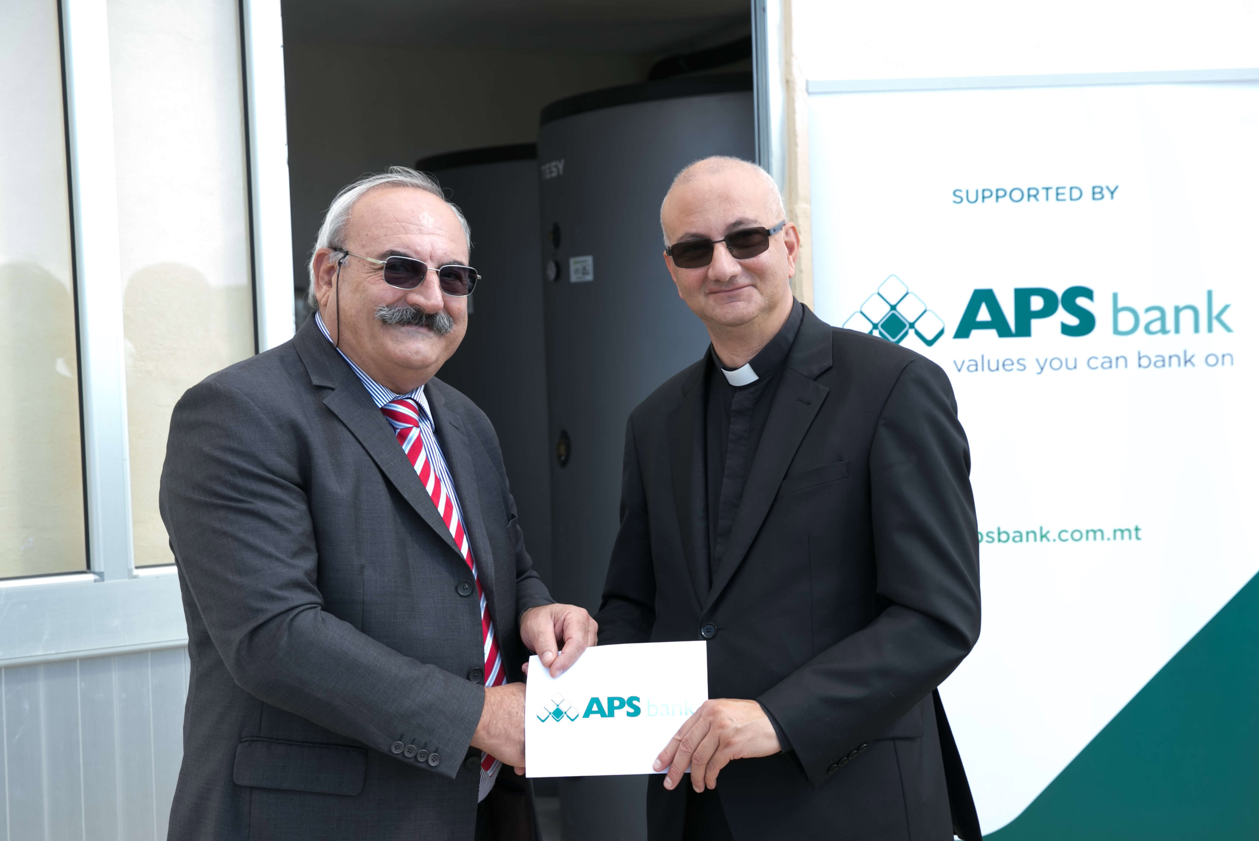 Frederick Mifsud Bonnici (APS Bank Chairmain) presenting the donation to Fr Martin Micallef.